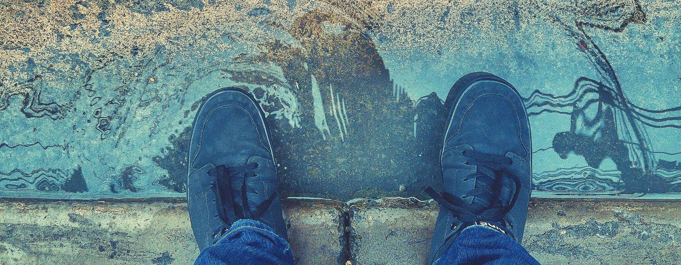 feet standing in a puddle by the sidewalk