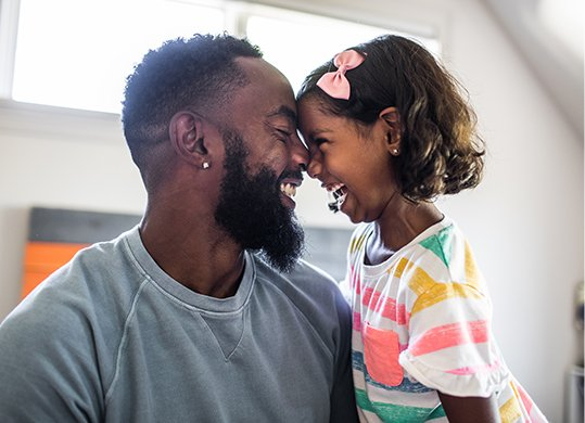 A father and daughter smiling